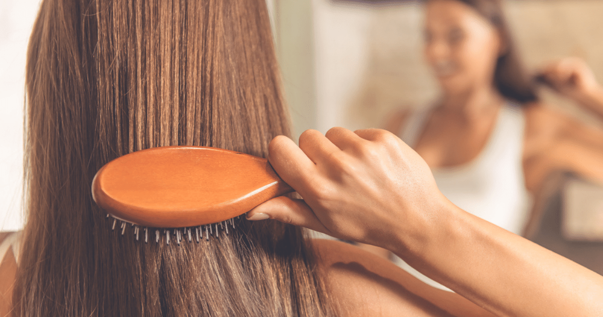 Middle aged woman brushing hair before storing wig
