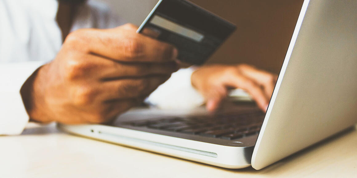 Image of person online shopping with credit card in hand