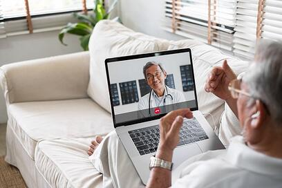 Patient on couch having telemedicine visit with doctor on laptop