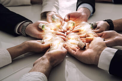 """This image showcases """"shared vision"""" with multiple hands in a circle each with an illuminated light bulb."""