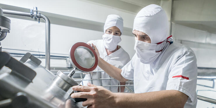 Employee examining industrial centrifuge for dairy production