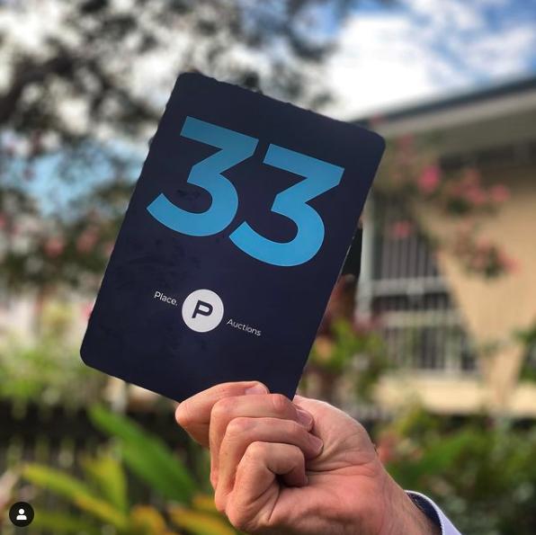 person holding an auction bidder's card