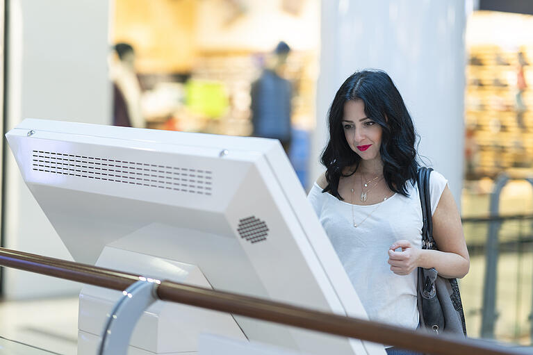 Woman looking at digital kiosk