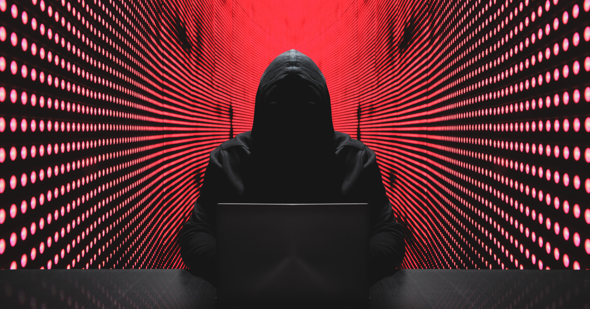 Image shows a cyber hacker's silhouette, with a red background behind them