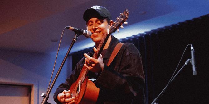 Ben Stewart smiling and playing guitar