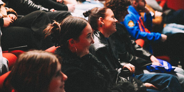 Students smiling while seated in auditorium