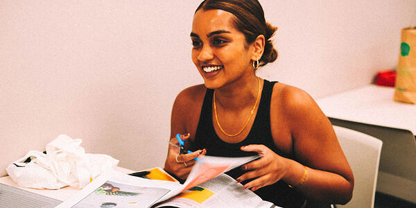 Girl cutting up magazine and smiling