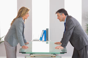 Two irritated businesspeople standing arguing on each side of a desk at office