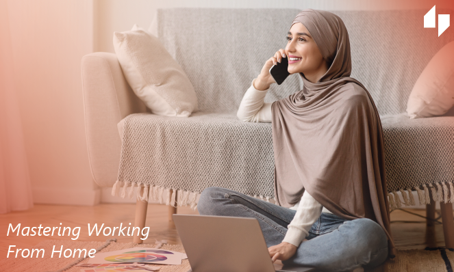 Woman sitting on the floor using a laptop and talking on the phone wearing a hijab and jeans sitting in front of a couch.