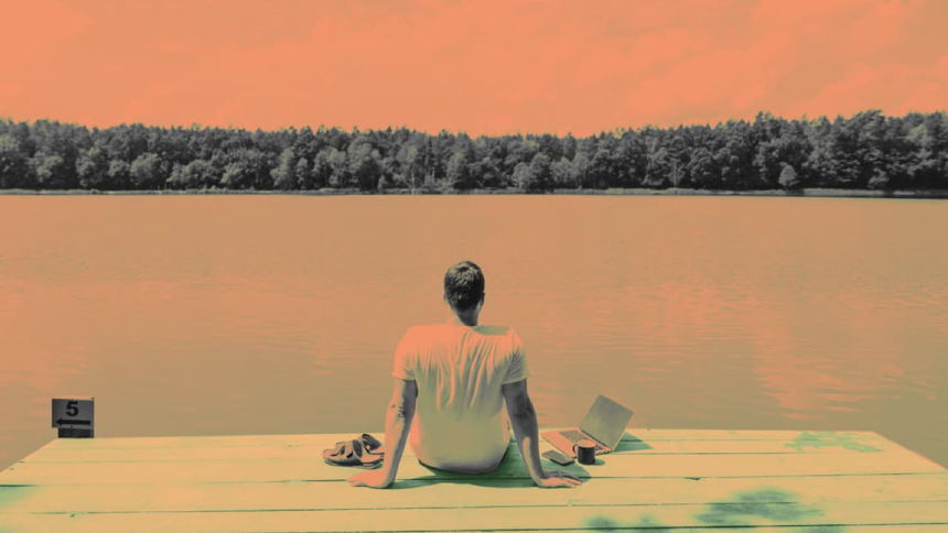 Man sitting on a dock facing a lake