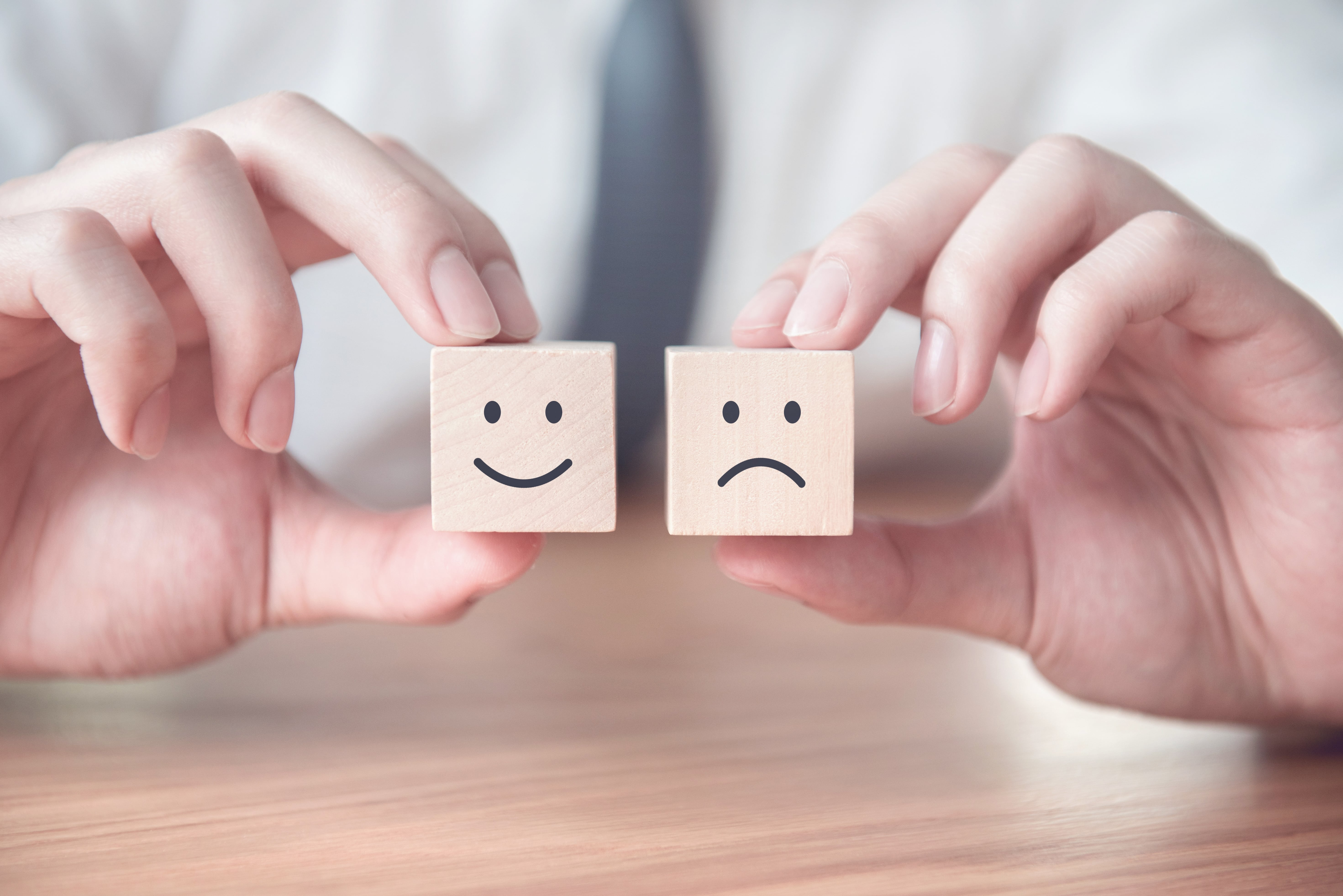 How to maintain momentum on mental health commitments with your company intranet - two cubes one with a happy face one with a sad face