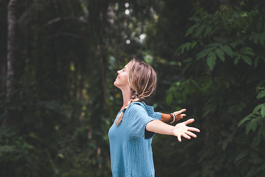 Woman in rainforest with arms outstretched breathing the air
