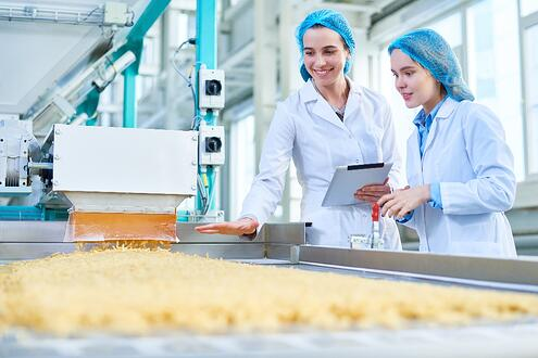 Two women in lab cotes in a factory analyzing a product