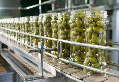 Olives in bottles in a factory