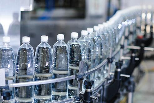 image of water bottles on assembly line, with information on their data