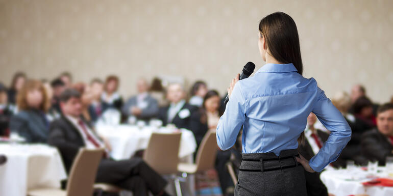 Organizadora de eventos empresariales hablando en público