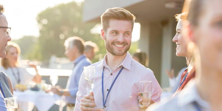 Profesionista en un evento corporativo sosteniendo una copa de vino