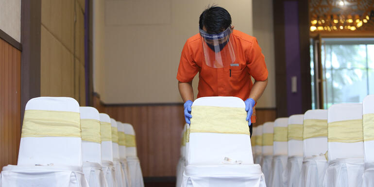 Personal de limpieza acomodando sillas de un evento conforme las reglas de distanciamiento social