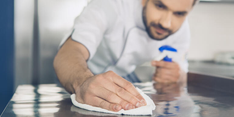 Cocinero limpiando una cocina para evitar alimentos contaminados