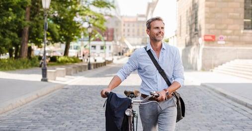 Man walking bicycle down street