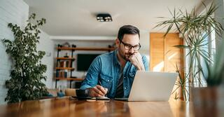 Photo of someone working from home at a laptop and writing notes