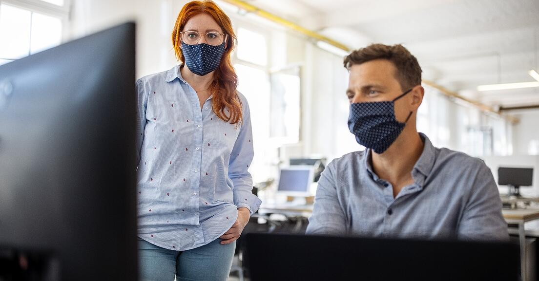 Two people in an office wearing face masks and looking at a computer monitor.