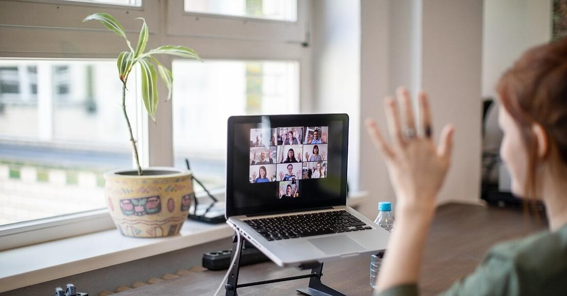 Photo of a person sitting at their desk in front of their laptop, on the screen of which is a remote meeting.