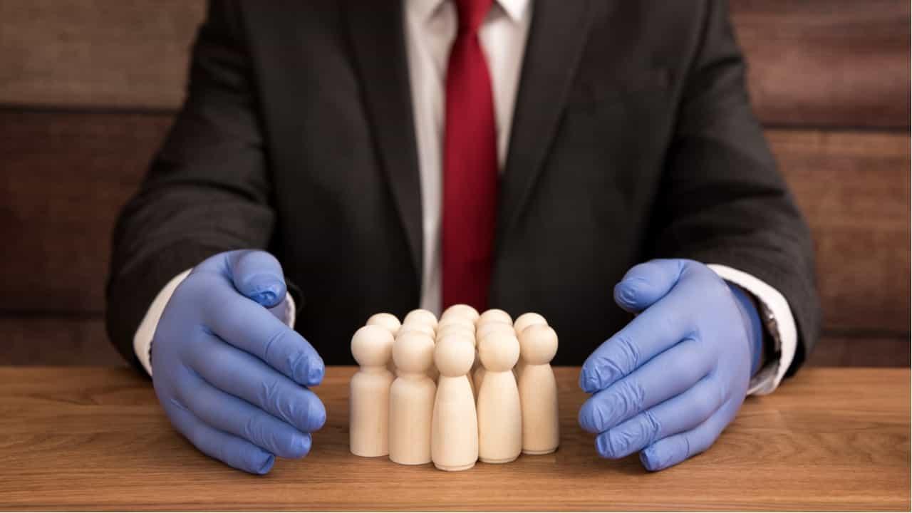 directivo con guantes protegiendo a su equipo del coronavirus