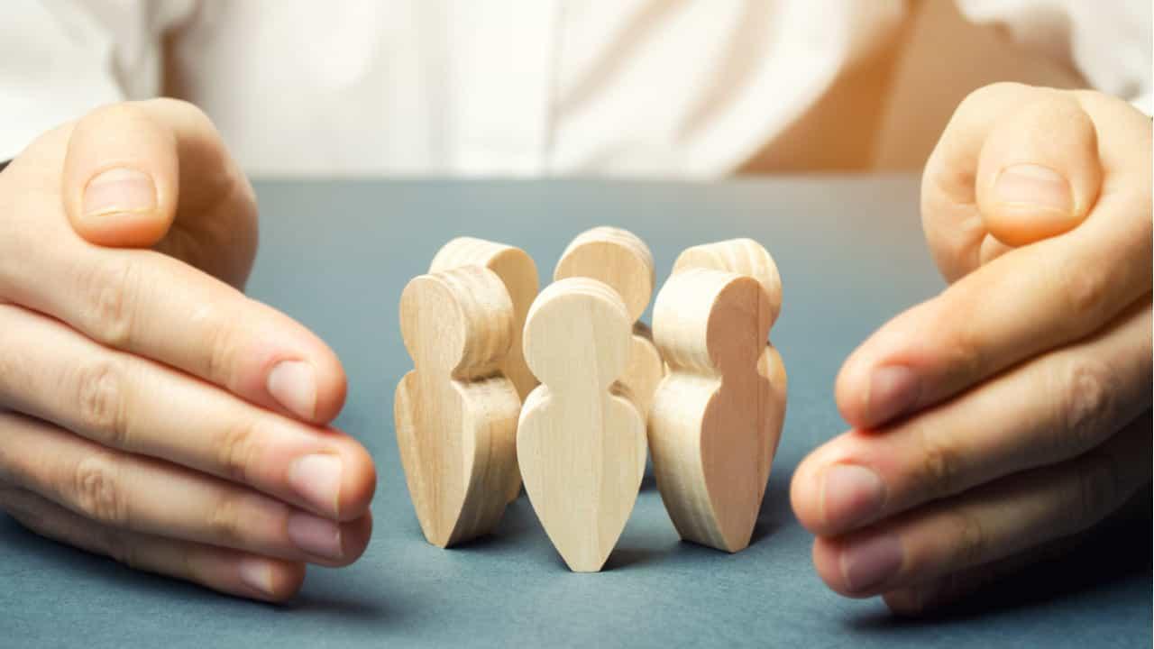 manos resguardando figuras de madera concepto de lider protegiendo a su equipo de la pandemia