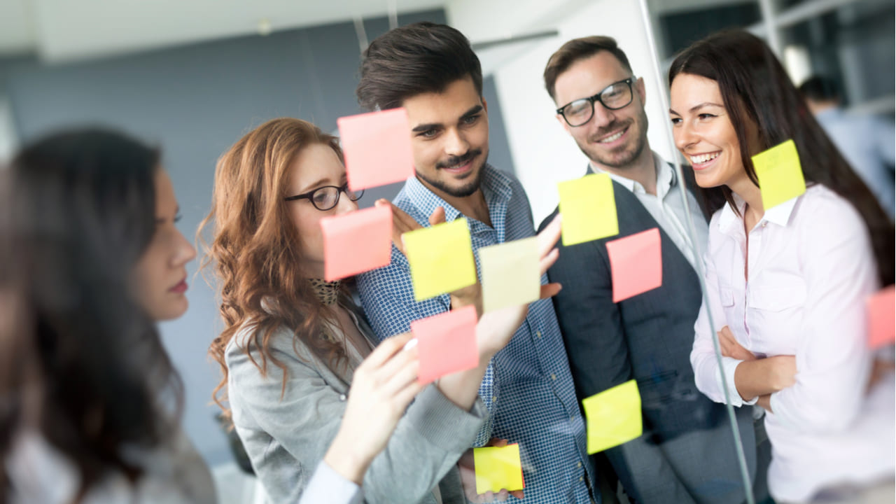 personas sonriendo y trabajando en grupo escribiendo en postits