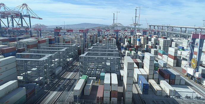 Automated yard cranes and reefers in the background