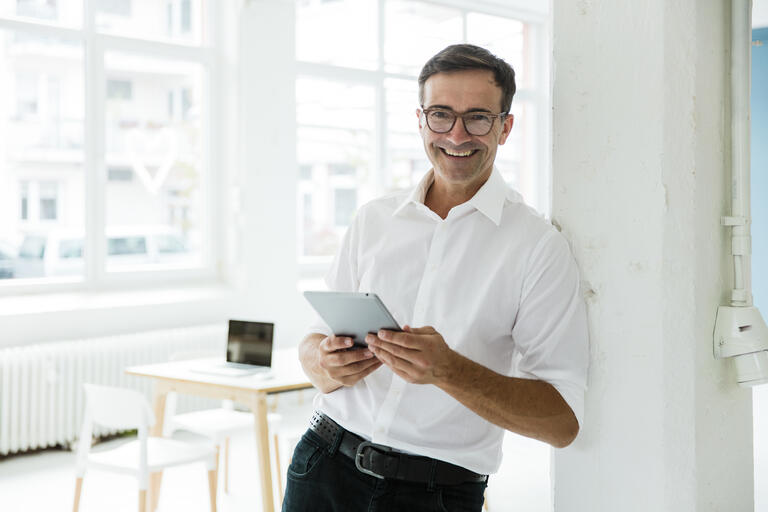 man smiling holding tablet and looking at camera
