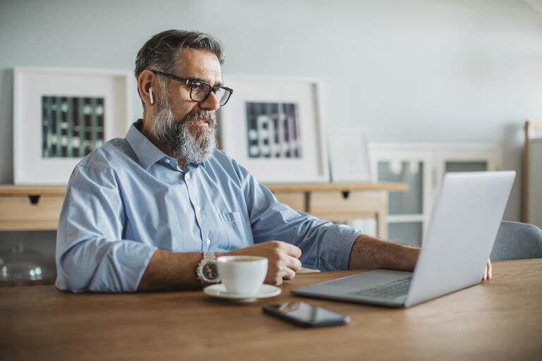 man drinking coffee and on laptop