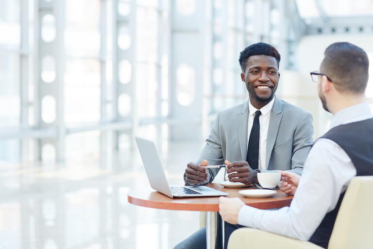 two men having coffee and talking