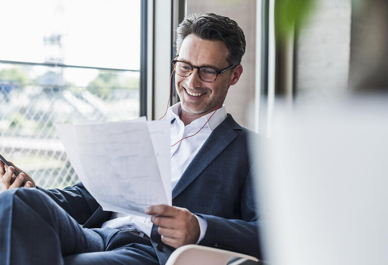 man smiling at papers