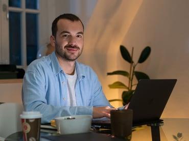Ein junger Mann sitzt an einem Tisch die Haende liegen auf seinem Laptop neben ihm steht eine Schale und ein Coffee to go Becher