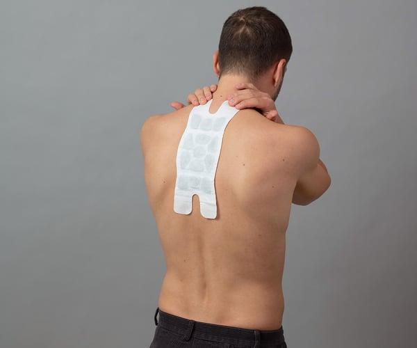 Mann mit freiem Oberkörper klebt ThermaCare® Wärmeauflage für größere Schmerzbereiche auf schmerzende Stelle zwischen den Schultern