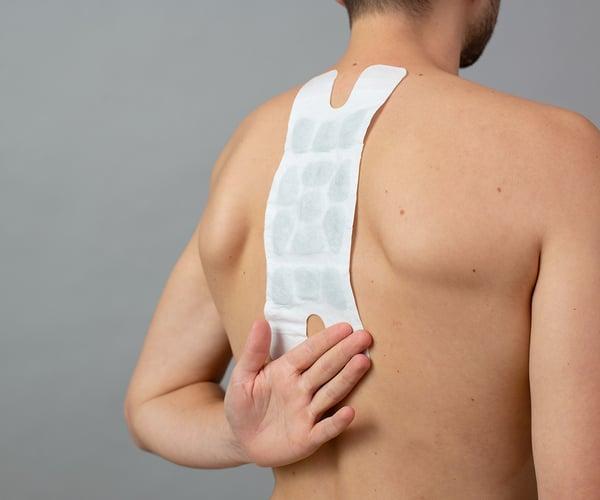 Mann mit freien Oberkörper fixiert ThermaCare® Wärmeauflage für größere Schmerzflächen mit dem Handrücken von unten auf der Haut