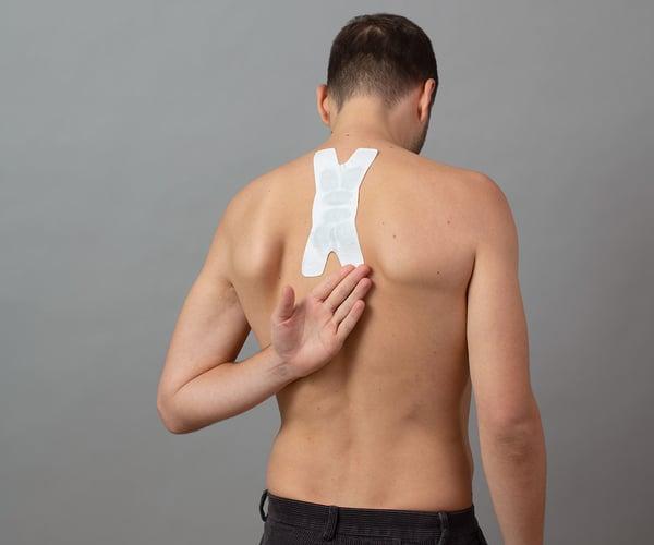 Mann mit freien Oberkörper fixiert ThermaCare® Wärmeauflage für flexible Anwendung mit dem Handrücken