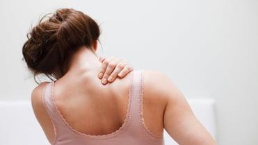 Eine Frau, mit dem Ruecken zur Kamera, fasst sich an die linke Schulter mit der rechten Hand