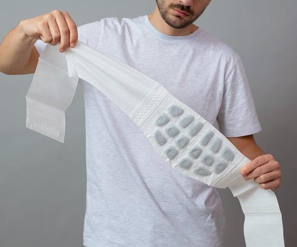 Mann in weißem T-Shirt klappt ThermaCare® Wärmeumschlag bei Rückenschmerzen komplett aus