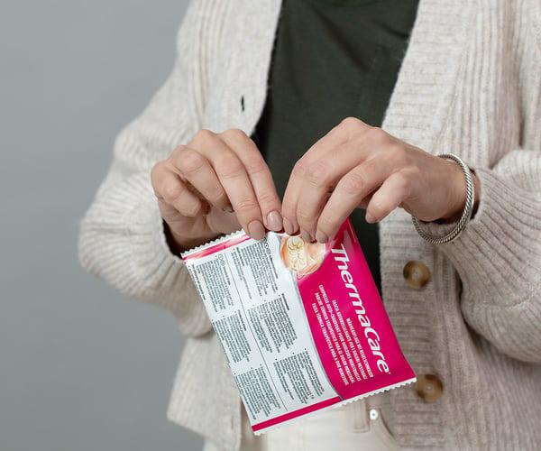 Frau öffnet Verpackung einer ThermaCare® Wärmeauflage bei Regelschmerzen