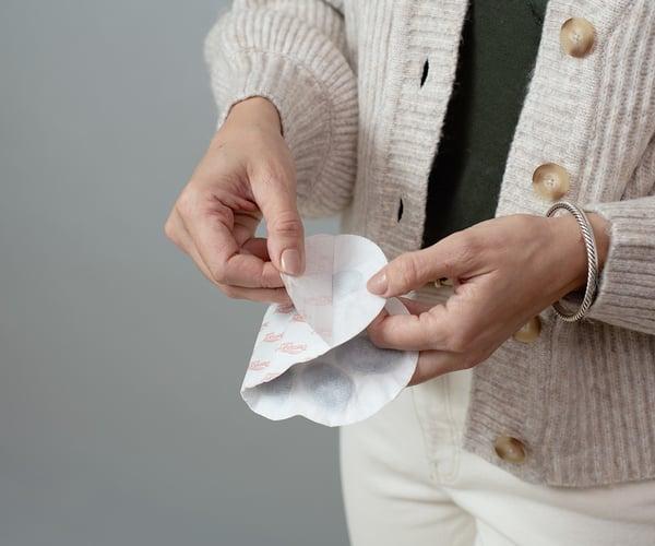 Frau entfernt Schutzfolie einer ThermaCare® Wärmeauflage bei Regelschmerzen