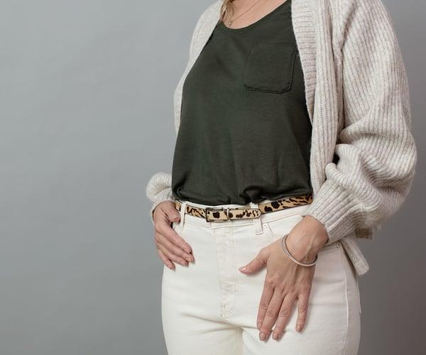 Frau mit grünem Oberteil und weißer Hose; ThermaCare® Wäremeauflage bei Regelschmerzen ist nicht zu sehen