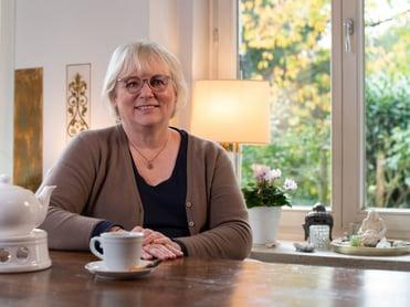 Eine Frau mittleren Alters mit Brille sitzt an einem Holztisch und trinkt Tee schmerzfrei mit ThermaCare Waermeumschlaegen ohne Chili