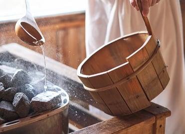 Eine Person mit umgebundenen Handtuch kippt Wasser auf heiße Steine in einer Sauna
