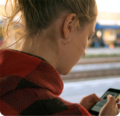 girl with phone outside browsing rounded new