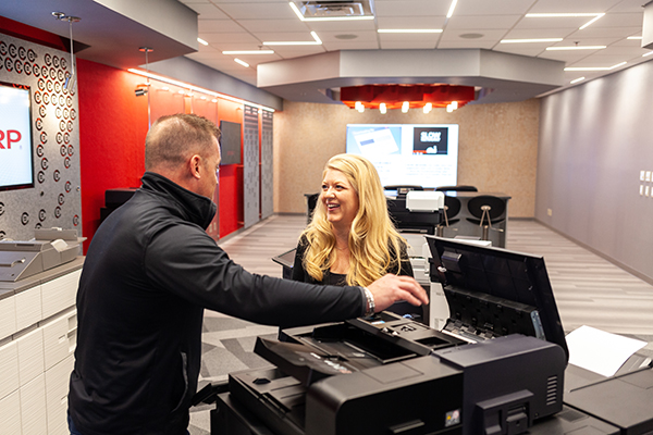Two people looking at a copier and printer