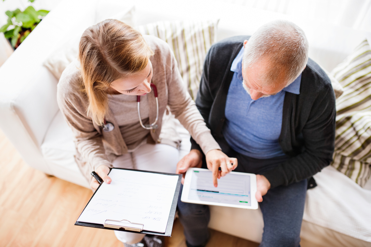 therapist with clipboard sitting next to aged man