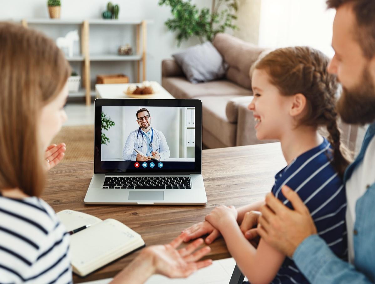 Familia frente a laptop en una teleconsulta con su médico